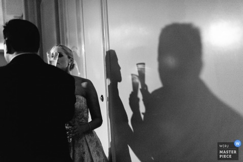 The shadows of the bride and groom enjoying champagne can be seen on the wall in this black and white photo by a San Antonio, TX wedding photographer.