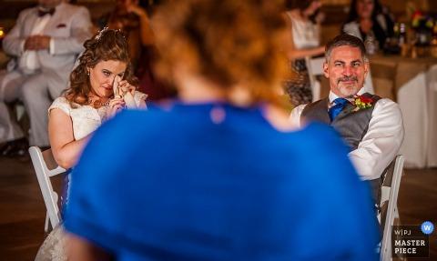 La mariée se déchire pendant qu'elle et le marié écoutent un discours dans cette image primée composée par un photographe de mariage documentaire de Charlotte, Caroline du Nord.