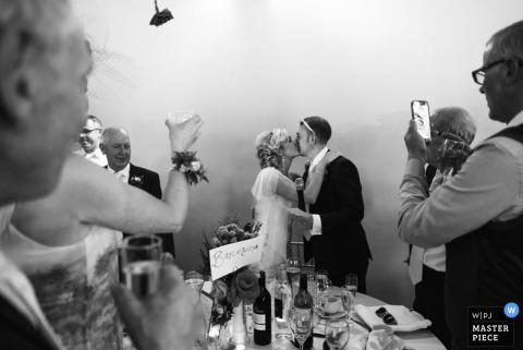 在英國大曼徹斯特婚禮報告攝影師拍攝的這張黑白照片中,客人們站在新娘和新郎身邊。