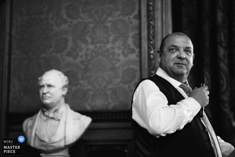 一名男子在接待期間發表講話,因為他站在英國大曼徹斯特報告攝影師拍攝的這張黑白婚禮照片的胸像旁邊。
