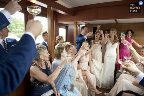 The guests toast the bride and groom in this award-winning wedding photo by a documentary-style Toronto, Ontario photographer.