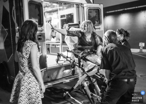 Although in good spirits, a wedding guest is taken by ambulance from the reception in this black and white photo captured by a Denver wedding photographer