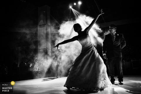 Fotograf ślubny w Limie wykonał to czarno-białe zdjęcie panny młodej, pokazując swoje ruchy taneczne za pomocą maszyny do mgły, gdy jej pan młody uśmiecha się do niej w pobliżu