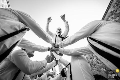 Pan młody wyskakuje w powietrze, gdy drużbowie łapią go na czarno-białej fotografii ślubnej skomponowanej przez mediolańskiego fotografa w stylu dokumentalnym.