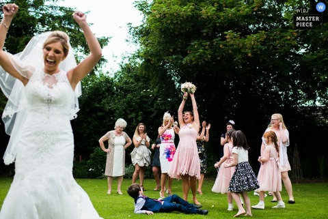 Nottinghamshire wedding photographer captured this photo of the bride tossing her bouquet to a group of women in the yard