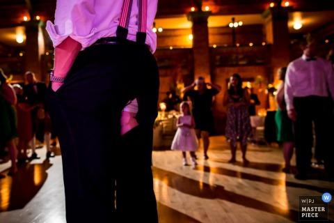 Fotograf ślubny w Chicago uchwycił to zdjęcie mężczyzny stojącego na parkiecie z rękami w kieszeniach po tym, jak rozerwał spodnie pokazując ruch