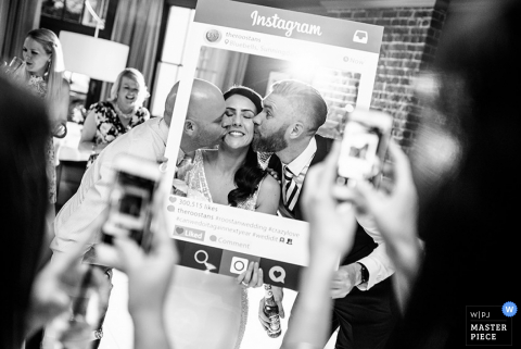 Guests hold up an Instagram frame as they take pictures of two men kissing the bride's cheeks through it in this black and white photo by a Hampshire, England wedding reportage photographer.