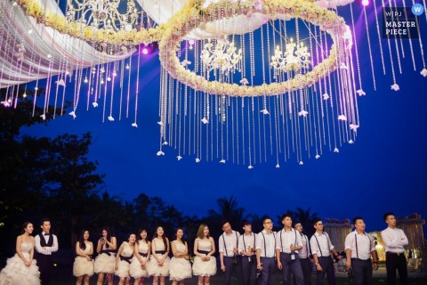 The bridal party stands outside beneath large lights in this wedding photo by a Hangzhou, China photographer.