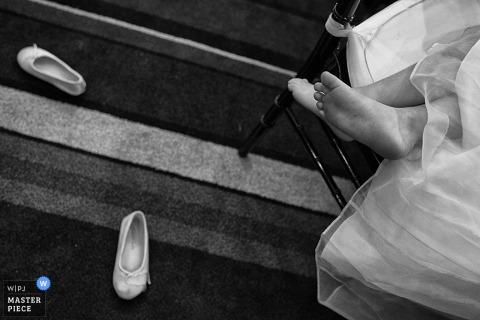 Photo détaillée d'une jeune fille assise sur une chaise, les chaussures ballottées sur le sol. Capturé par un photographe de mariage primé de Carson City, NV.