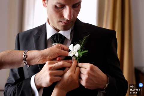 A woman helps the groom pin on his boutonniere in this image created by a Calabria documentary wedding photographer.