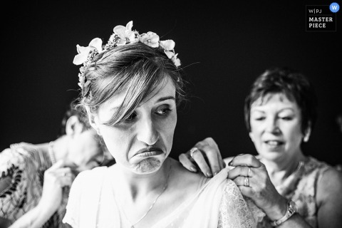 De bruid maakt een gezicht terwijl twee vrouwen haar helpen met haar jurk in deze zwart-witfoto door een trouwfotograaf uit Lille, Frankrijk.