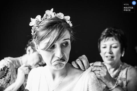 A noiva faz uma cara quando duas mulheres a ajudarem com seu vestido nesta foto preto e branco por um fotógrafo do casamento de Lille, France.