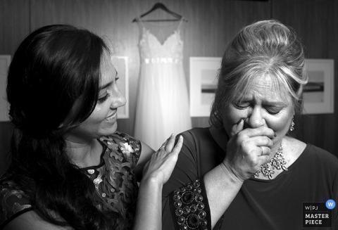 Une femme est émue avant la cérémonie alors que la robe de mariée de la mariée est suspendue derrière elle sur cette photo noir et blanc d'un photographe de mariage de Chicago, IL.