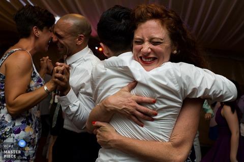 Le photographe de mariage de Carson City a capturé cette photo émotionnelle de la mariée et du marié dansant avec les membres de leur famille