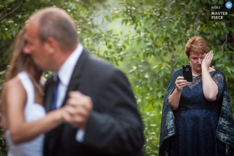 Montana wedding photographer captured this photo of the mother of the bride crying while capturing the father daughter dance on cellphone video