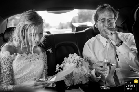 Atlanta wedding photographer captured this black and white photo of the bride riding in the car with her father on the way to the ceremony, smiling as she reads a letter and her bouquet rests beside her
