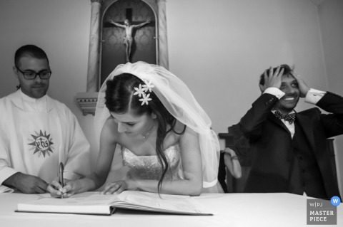 The groom grabs his head and smiles while the bride signs a book in front of the priest in this black and white photo by a Lombardy wedding photographer.