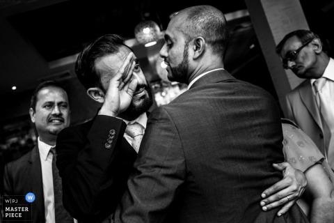 倫敦婚禮攝影師拍攝了這張黑白照片,當他在儀式前擁抱他的兄弟時,新郎擦乾眼淚