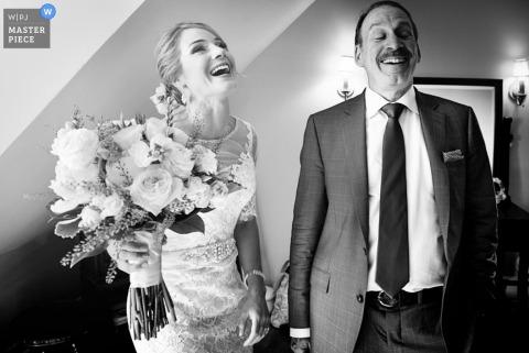 Die Braut und ihr Vater stehen in diesem Schwarzweißfoto, das von einem Hochzeitsfotografen aus Montreal, Quebec, im Stil eines Dokumentarfilms verfasst wurde, zusammen und lachen.