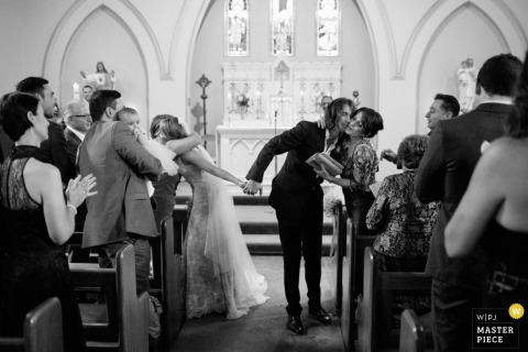 Guests hug the bride and groom as they exit the ceremony in this black and white image captured by a New South Wales, Australia wedding photographer.