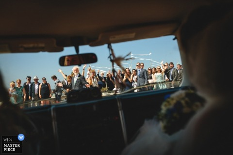 Zuid Holland wedding photographer captured this image of the wedding guests as seen from the backseat as the bride and groom drive off to their honeymoon