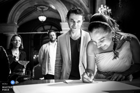 The bride smiles while she signs the marriage license in this black and white image created by a Rome documentary wedding photographer.