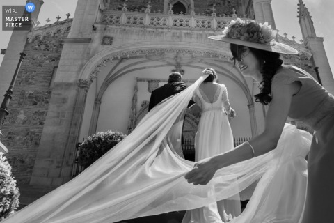 Madrid wedding photographer captured this black and white photo of the bride getting some help with the train on her gown as she walks into the church