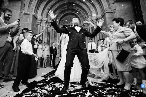 The bride and groom exit the ceremony as guests throw rice and celebrate in this black and white wedding picture composed by a Braga, Portugal documentary photographer.