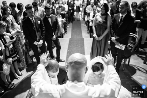 The priest holds his hands over the bride and groom as they kneel at the altar in this black and white photo taken by a documentary-style Tuscany wedding photographer.