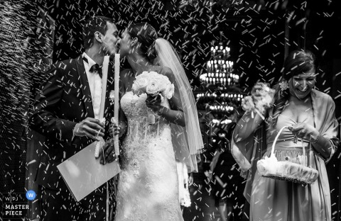The bride and groom kiss while guests toss rice in this black and white photo captured by a Sofia, Bulgaria wedding photographer.