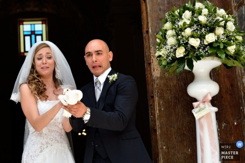 Caserta wedding photographer captured this photo of the bride and groom hesitantly releasing the dove after their ceremony