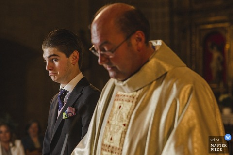 The groom makes a face while he stands next to the priest in this photo by a Madrid, Spain wedding photographer.