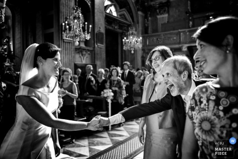 A man leans over to grab the bride's hand after the ceremony in this black and white photo by a Tuscany wedding photographer.