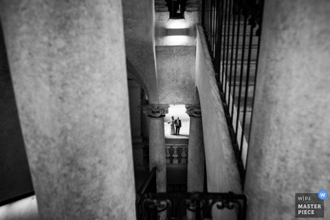The bride and groom can be seen standing outside from the top of a staircase in this black and white wedding photo by an award-winning Piedmont photographer.