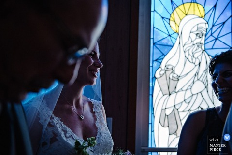 Hudson Valley wedding photographer captured this photo of a bride smiling as the sun shining through the stained glass window beside her cast a blue glow on her dress