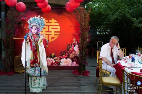 A woman dressed in traditional dress performs during the reception in this photo by a Beijing, China wedding photographer.