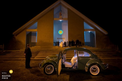 A green Volkswagen waits outside for the bride and groom as they exit the ceremony in this image created by an award-winning Santa Catarina, Brazil wedding photographer.