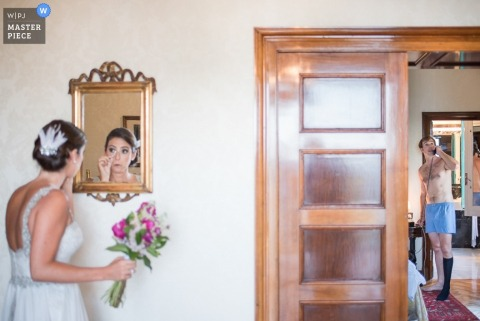 Lima wedding photographer captured this photo of the bride in her gown checking her make up in a mirror directly outside of a room where we can see the groom in a state of undress, not quite ready for the ceremony