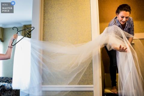 Dwie kobiety niosą welon panny młodej na tym zdjęciu ślubnym autorstwa wielokrotnie nagradzanego fotografa z Chicago.