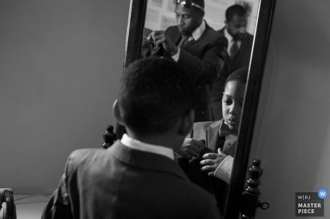 Der Hochzeitsfotograf aus Baltimore hat dieses Foto eines jungen Trauzeugen aufgenommen, der seinen Boutonniere im Spiegel überprüft, während ältere Trauzeugen im Hintergrund zu sehen sind