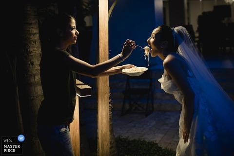 Una mujer alimenta a la novia con un poco de espagueti en esta foto capturada por un fotógrafo de bodas en Madrid, España, de estilo documental.