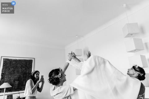 Frankreich-Hochzeitsfotograf nahm dieses Schwarzweiss-Foto der Brautjungfern gefangen, die der Braut helfen, ihr Kleid anzuziehen