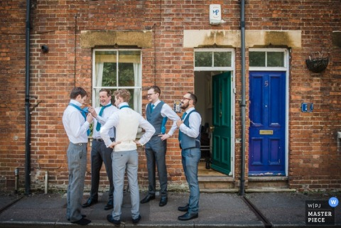 The groomsmen stand outside getting ready for the ceremony in this award-winning image by a Manhattan, NY wedding photographer.