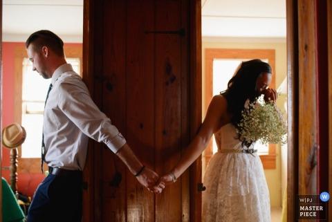 Braut und Bräutigam halten Hände zwischen zwei getrennten Räumen, während sie versuchen, sich auf diesem Hochzeitsbild, das von einem preisgekrönten Fotografen aus Outer Banks, NC, aufgenommen wurde, nicht anzusehen.