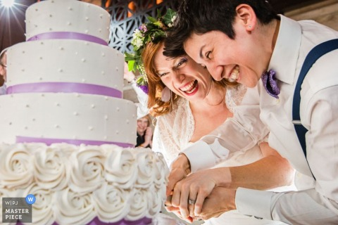 New Jersey wedding photographer captured this photo of the couple ecstatically cutting into their four tier wedding cake