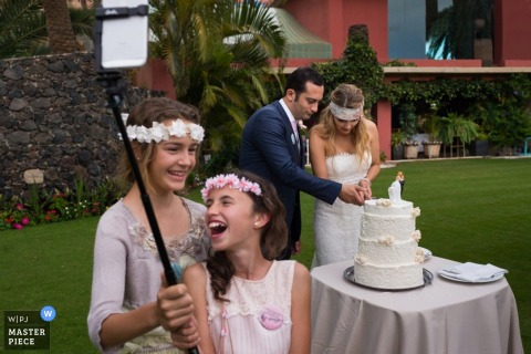 Madrid wedding photographer captured this photo of two young girls using a selfie stick to capture an image with the bride and groom as they cut the cake