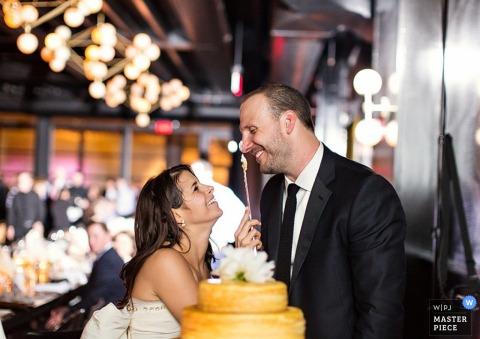 De bruidegom lacht terwijl de bruid een beetje cake op zijn neus gooit in dit huwelijksbeeld, gecomponeerd door een bekroonde Brooklyn, NY-fotograaf.