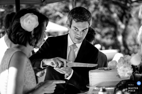 Los Angeles wedding photographer captured this black and white photo of the groom holding a knife as he shows the bride exactly how he would cut the cake