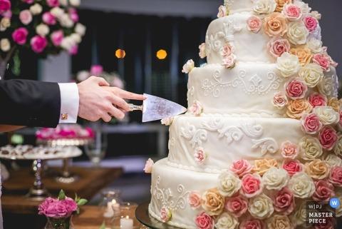Minas Gerais wedding photographer captured this detail shot of a groom and bride slicing into a pink and cream flower adorned cake