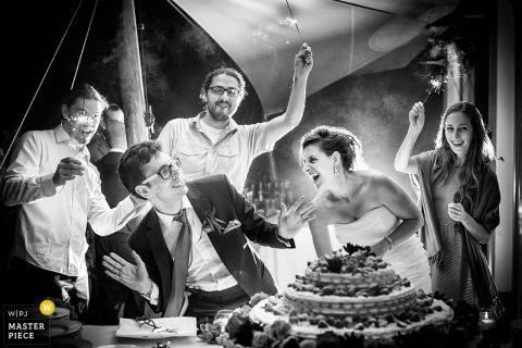 Arezzo wedding photographer captured this black and white image of the bride and groom getting ready to dig into their cake as guests hold sparklers nearby